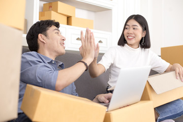 Asian couple people looking to with success felling. People with SME, Delivery, Online Business success concept.