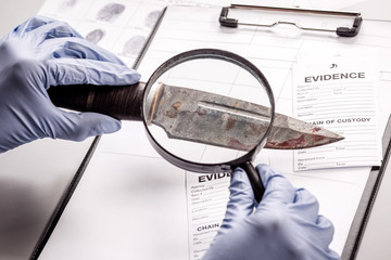 Detective through a magnifying glass looking at a evidence