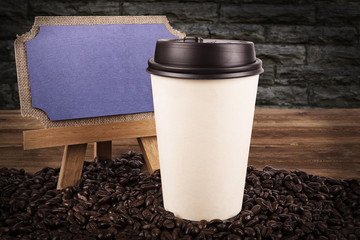 Cup of coffee and coffee beans on an old wooden table, brick wall in background.