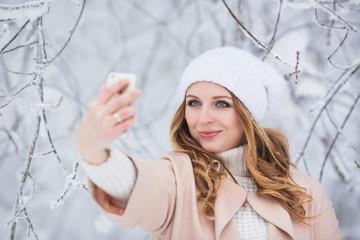 Portrait of young woman in a beige dress does a selfie in a winter