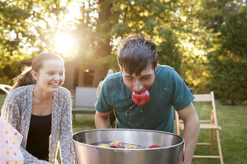 Teenage boy, apple in mouth, apple bobbing at garden party