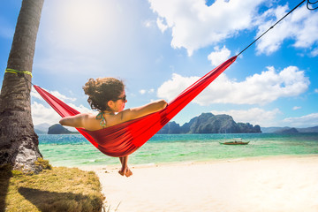 Young caucasian female relaxing in a red hammock on a tropical b