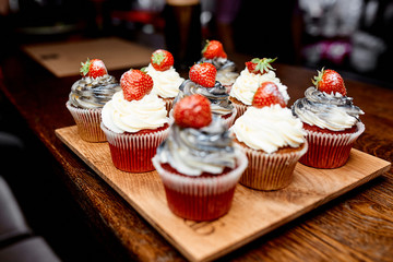 Photo of sweet cakes with strawberry on the table