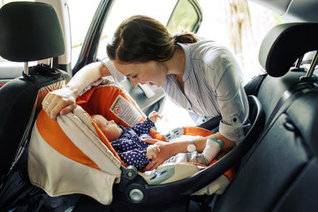 Happy woman with infant seating in baby chair in car
