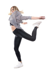 Young woman jazz dancer in striped shirt and leggings jumping on one leg with arms behind. Full body length portrait isolated on white background.
