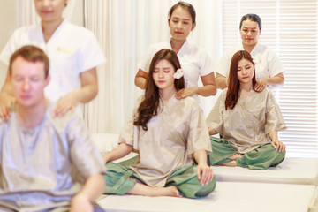 A young man and two women getting Thai massage sitting in the same room.