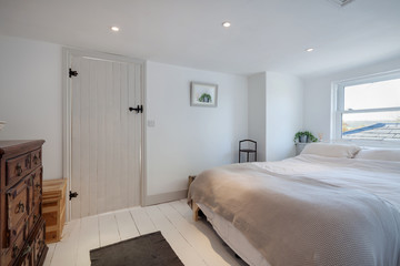 Minimalist cottage bedroom decorated in white