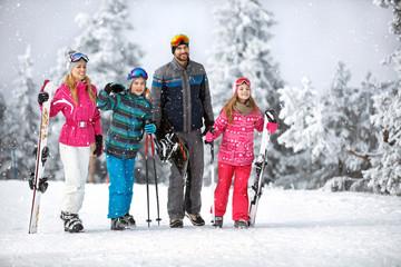 Family going to ski terrain with ski equipment