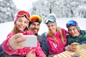 Girl with family taking selfie while resting from skiing