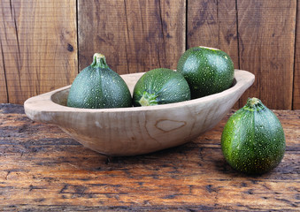 round zucchini in a wooden bowl on plank