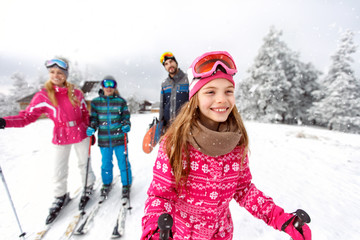 Girl skier skiing with family on mountain