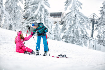 Boy helps to girl to get up from snow with skis