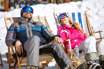 Smiling couple on break from skiing enjoy on sun