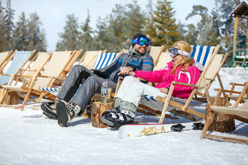 Skiers couple in sun lounger enjoy on sun
