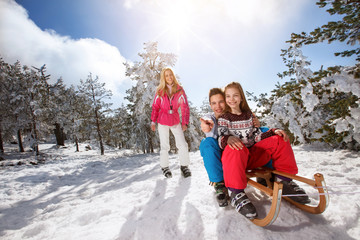 Male and female child sitting on sled in snowy nature
