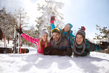Family on winter vacation lying on snow and enjoy