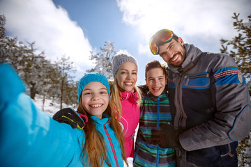 Happy children with parents on skiing