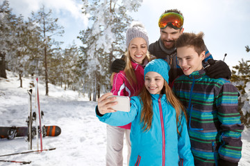 Girl taking selfie with family on skiing