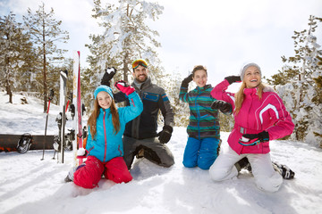 Family making snow balls on skiing in mountain