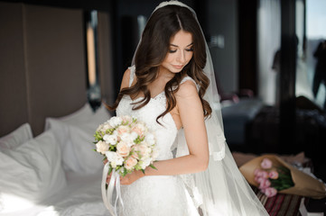 portrait of glamour bride in elegant wedding dress,veil and bouquet