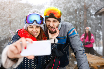 Skiers couple outdoor taking selfie.