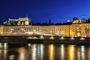 Austria, Salzburg, Riverbank with buildings at night