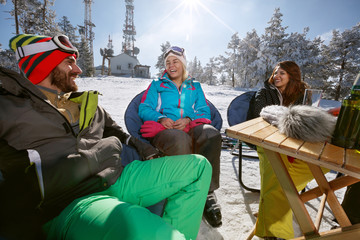 Male and female skiers talking and smiling in cafe on ski terrain