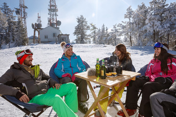 Skiers resting from skiing in cafe on ski terrain