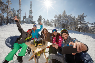 Skiers in cafe outdoor taking selfie