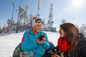 Young women drinking tea in cafe on skiing