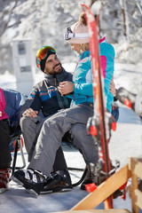 Woman on skiing sitting in man's lap