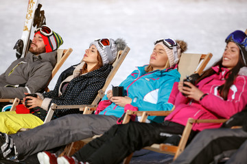 Skiers group sunbathing in sunbed on ski terrain