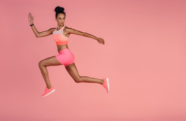 Healthy african woman sprinting on pink background