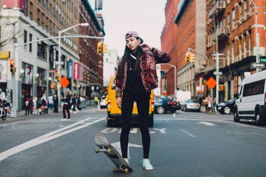 Female skateboarder on street in New York City, USA
