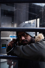 Man with handset in telephone box.