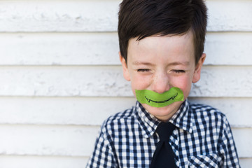 Little boy with a monster smile taped on his face