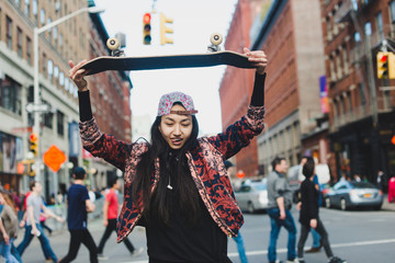 Cool young woman in city with skateboard