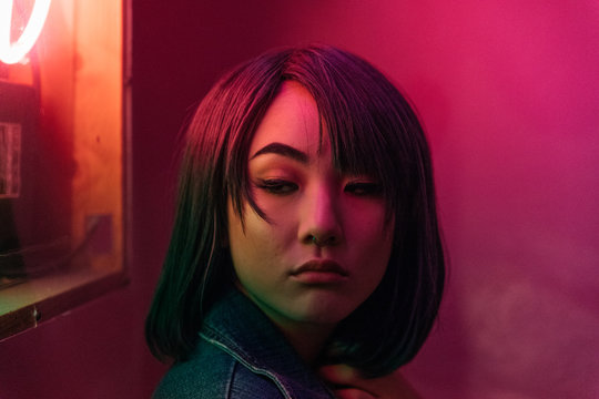 Portrait of young asian female woman in pink room with neon lights