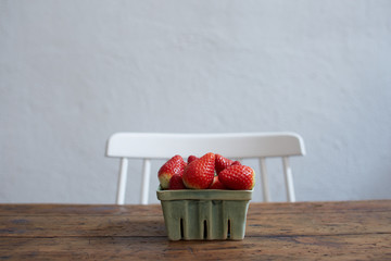 Ceramic basket with strawberries on a wooden old table