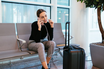 Business woman at the airport with her mobile phone