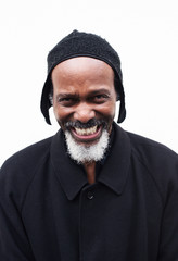 Laughing man in black hat over white background.