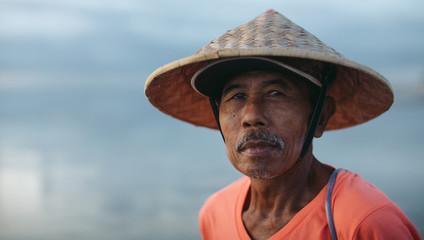 Old balinese fisherman working at sunrise