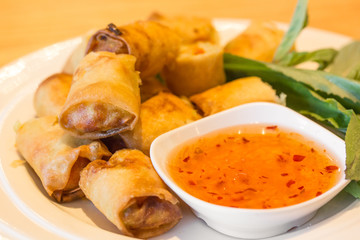 Fried spring rolls with sauce.