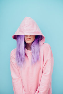 Young woman with blue dyed hair in pink hoodie