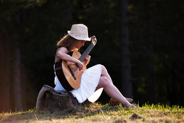 Young girl playing guitar in park