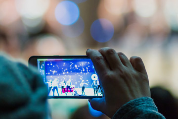 A woman records a video or photographs the performance of artists on stage using her phone. Hand close-up. Blurry. Bokeh. Copyspace.