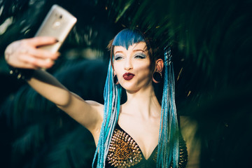 Goth girl taking a selfie in tropical garden