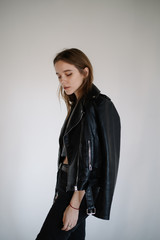 beautiful young girl in a leather jacket on a gray background