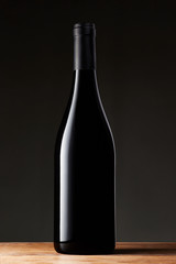 Black wine bottle isolated on black background
