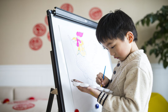 little asian boy drawing rooster indoor